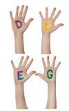 Алфавит (письма) покрашенный на руках детей Поднимают вверх руки стоковые фото
