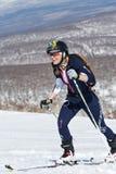 Альпинизм лыжи, вертикальная гонка: усмехаясь альпинист лыжи девушки взбирается на лыжах на горе Стоковые Изображения