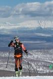Альпинизм лыжи, вертикальная гонка: усмехаясь альпинист лыжи девушки взбирается на лыжах на горе Стоковые Фото
