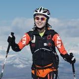 Альпинизм лыжи, вертикальная гонка: усмехаясь альпинист лыжи девушки взбирается на лыжах на горе Стоковое Фото