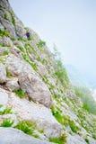 2 альпиниста взбираются путь высекаенный в отвесный утес Стоковая Фотография