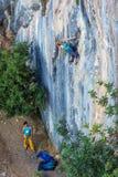 2 альпиниста работают в парах на вертикальной скалистой стене Стоковые Фотографии RF