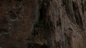 Альпинист взбираясь скала с страхованием сток-видео
