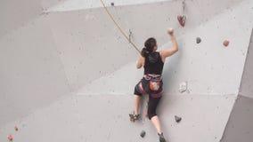 Альпинист девушки с взбираясь оборудованиями движение медленное молодая атлетическая девушка взбирается на утесе на взбираясь сте видеоматериал