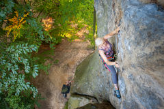 Альпинист утеса женщины взбирается на скалистой стене Стоковые Изображения