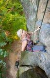 Альпинист утеса женщины взбирается на скалистой стене Стоковое Изображение
