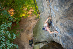 Альпинист утеса женщины взбирается на скалистой стене Стоковое Изображение RF