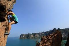 Альпинист утеса женщины взбираясь на утесе горы взморья Стоковые Фото