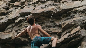 Альпинист утеса оценивает гору для того чтобы взобраться сток-видео