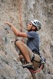 Альпинист человека льнуть к скале Стоковая Фотография