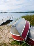 2 алюминиевых шлюпки вытянули вверх на береге с доком на заднем плане Стоковая Фотография