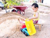Баба играя игрушку около кучи песка Стоковые Изображения