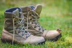 Бабочка отдыхает на ботинке ` s солдата Стоковое фото RF