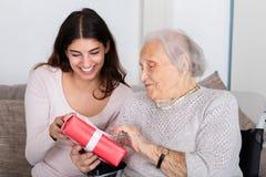 Бабушка давая подарок к ее внучке стоковое изображение