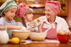 Бабушка, внук и шеф-повар внучки выпечка в кухне Стоковые Изображения