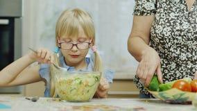 Бабушка внучки посещая 6-ти летняя девушка ест салат Рядом с ей, женщина пожилых людей подготавливает еду - акции видеоматериалы