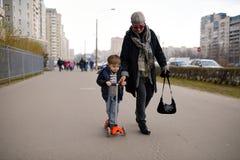 Бабушка вытягивает внука на улице самоката вниз Стоковое Фото