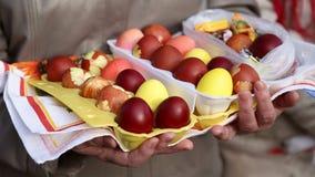 Бабушка держит пасхальные яйца