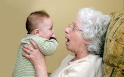 Бабушка играя с маленьким младенцем