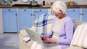 Бабушка используя компьтер-книжку видеоматериал