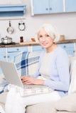 Бабушка используя портативный компьютер стоковые изображения rf