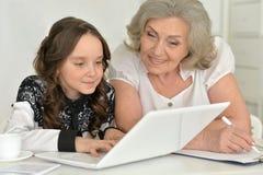 Бабушка и внучка делая домашнюю работу Стоковое Изображение