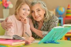 Бабушка и внучка делая домашнюю работу Стоковые Фото