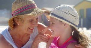 Бабушка и внучка играя друг с другом на пляже сток-видео