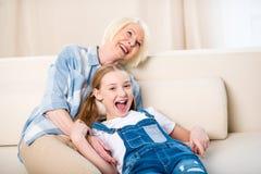 Бабушка и внучка имея потеху совместно на софе Стоковое Изображение RF