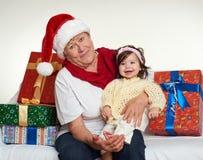 Бабушка и внучка одели в santa шляпа с подарочными коробками сидит на софе, белой предпосылке Канун Нового Годаа и праздник c рож стоковая фотография