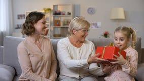 Бабушка и дочь давая настоящий момент школьнице, заботу материнства, л сток-видео