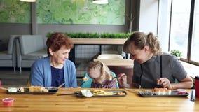 Бабушка и мать кормят маленькую девочку в поворотах сток-видео