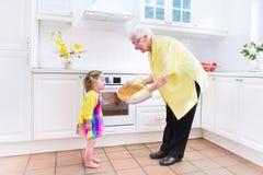 Бабушка и смешной пирог выпечки девушки в белой кухне Стоковое фото RF