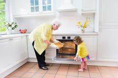 Бабушка и сладостный пирог выпечки девушки в белой кухне Стоковая Фотография