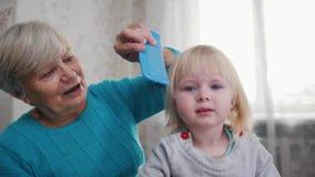 Бабушка наслаждается расчесывать волосы к ребенку на солнечном утре Полезного время работы дома стоковое изображение rf