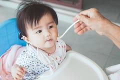Бабушка подавая милый азиатский ребёнок с ложкой Стоковые Изображения