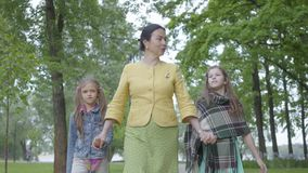 Бабушка портрета зрелая идя в красивый зеленый парк с 2 милыми внучками держа руки с ними и видеоматериал