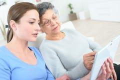 Бабушка порции молодой женщины используя таблетку Стоковое Изображение