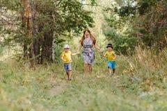 Бабушка при 2 внука бежать в парке стоковое изображение rf