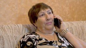 Бабушка, старуха использует Smartphone, конец вверх сток-видео