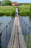 Бабушка с велосипедом и сумки на висячем мосте над рекой Стоковое Изображение RF