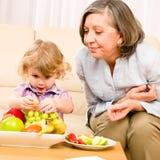 Бабушка с внучкой ест плодоовощ дома Стоковые Изображения RF