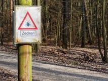 БАВАРИЯ FORCHHEIM, ГЕРМАНИЯ - 2-ОЕ АПРЕЛЯ 2019 - видная опасность подписывает в лесе, предупреждающих посетителях тиканий стоковая фотография rf