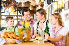 Баварская девушка с семьей в ресторане Стоковое Фото