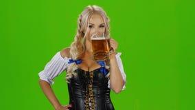 Баварская женщина выпивая стекло пива показывая большие пальцы руки вверх и подмигивать зеленый экран акции видеоматериалы