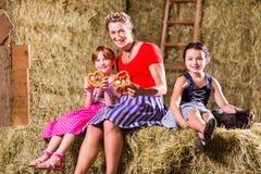 Баварская семья сидя на сеновале с кренделями Стоковые Изображения