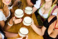 Баварские девушки выпивая пиво стоковое фото