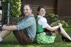 Баварские пары сидя в траве Стоковые Изображения