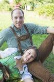 Баварские пары сидя на траве Стоковая Фотография