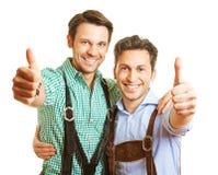 2 баварских люд держа большие пальцы руки вверх Стоковые Фотографии RF